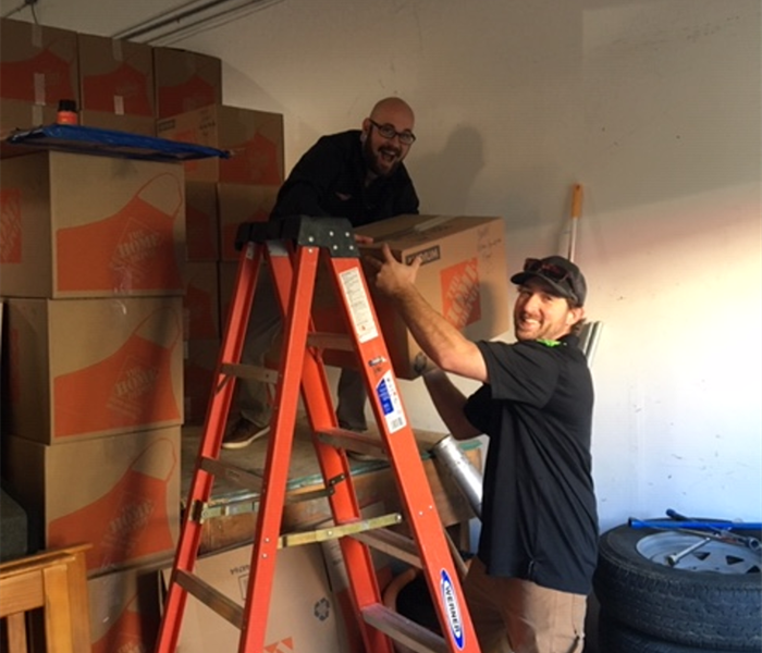 Picture shows two employees on ladder packing boxes